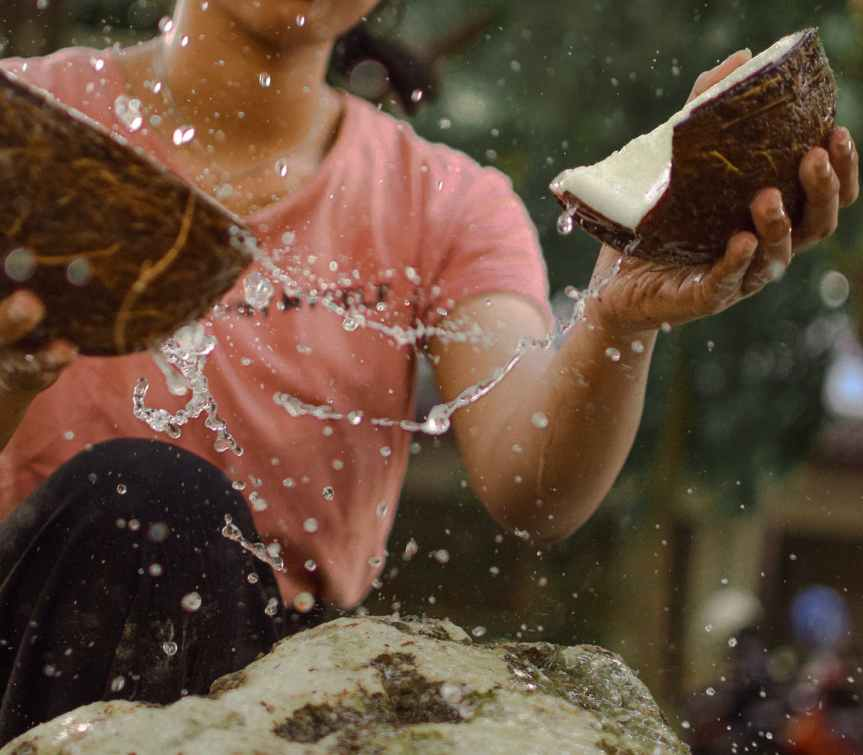 photo of woman cracking coconut shells