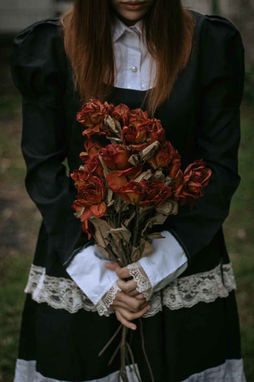 woman in a black dress oddly holding a dry bouquet of roses